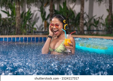 Screaming with joy, an interracial brunette is enjoying in the pool with a cocktail in her hand, in yellow headphones and a wristwatch, yellow-pink sunglasses raised by her hand, a green bikini.