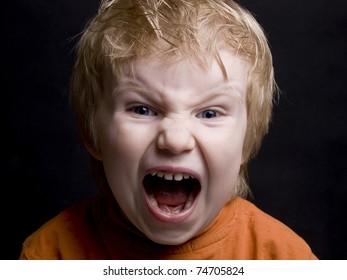 Screaming little blond  boy on black background
