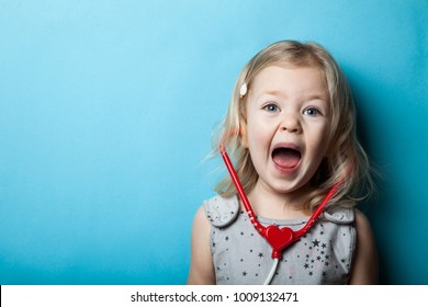 Screaming little girl with a toy stethoscope on a blue background. Emergency. Copy space.