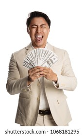 Screaming man in a bright suit holding a big fan of money. White background.