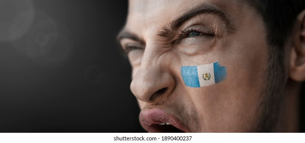 A screaming man with the image of the Guatemala national flag on his face.