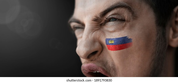 A screaming man with the image of the Liechtenstein national flag on his face.