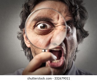 Screaming man looking through a magnifying glass