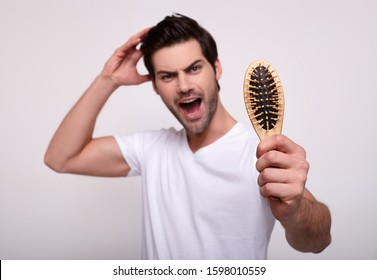 A screaming man screams in fear, holds a comb and touches his chic black hair. Men's problem of hair loss, dandruff. Male pattern baldness.