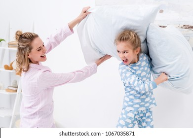 screaming mother and daughter having fun and fighting with pillows at home