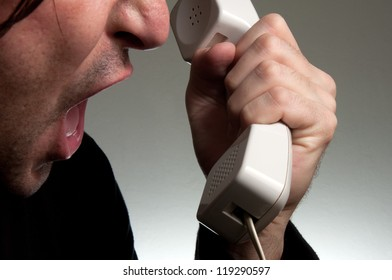 Screaming on the phone. Man in black shirt screaming on the telephone during the conversation.