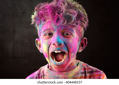 Screaming portrait of boy with face smeared with colored powder in a dark background. Concept for Indian festival Holi.
