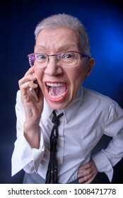 Screaming senior business woman angry with a person she't talking to on her phone