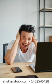 Screaming shocked Vietnamese man holding his head when reading e-mail on laptop screen