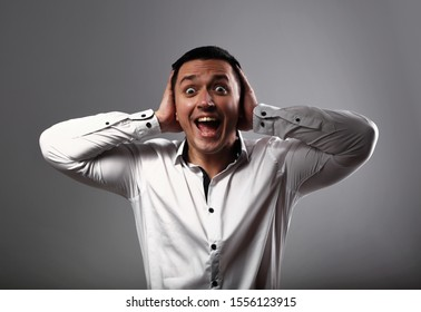 Screaming shocked young business man looking with wide open mouth and holding the hands the head on grey background. Closeup emotion portrait
