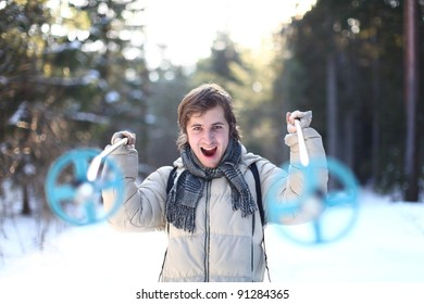 Screaming skier with cross-country poles on sunny winter day in the forest (focus on young man)