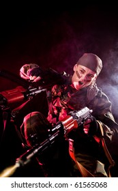 Screaming soldier shooting his enemies, studio shot over black background