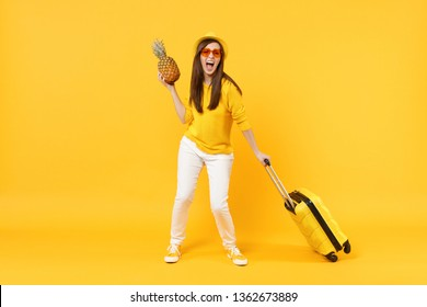 Screaming traveler tourist woman in summer clothes hat hold fresh ripe pineapple fruit isolated on yellow orange background. Passenger traveling abroad on weekends getaway. Air flight journey concept