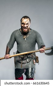 Screaming viking with his axe on the grey background