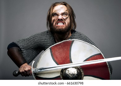 Screaming viking with his sword and shield on the grey background