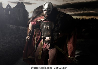 Screaming viking warrior with sword, armour and helmet before castle and sunset