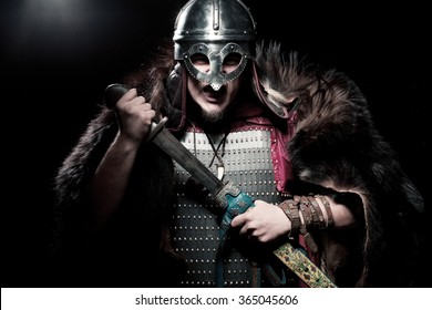 Screaming viking warrior with sword, armour and helmet over black background