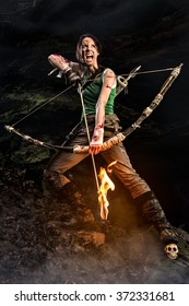 Screaming woman dressed up as Lara Croft holds a bow and pulls the bowstring with a burning arrow.