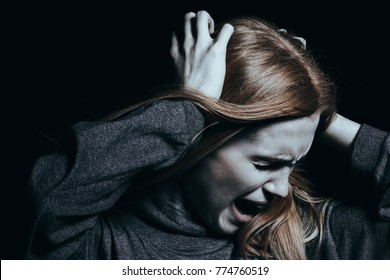 Screaming woman with hallucinations and psychosis against black background