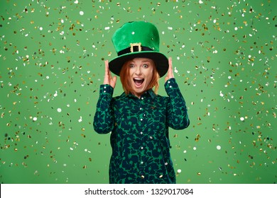 Screaming woman with leprechaun's hat under a shower of confetti