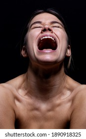 Screaming woman on a black background. Young woman's face with mouth open while screaming isolate from black. She is frustrated and in emotional pain. She is stresed and mad.