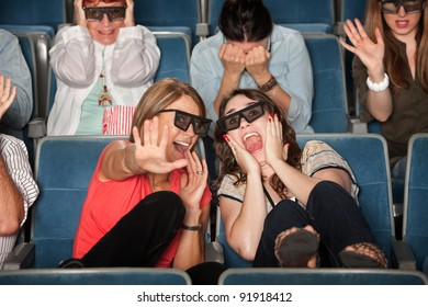 Screaming women with 3D glasses cower in chairs