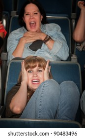 Screaming women watch scary movie in theater