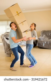 screaming young couple with falling stack of boxes
