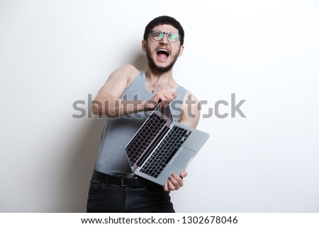 99c57f438a1 Screaming young guy opening laptop over white background. Wearing t-shirt  and black jeans