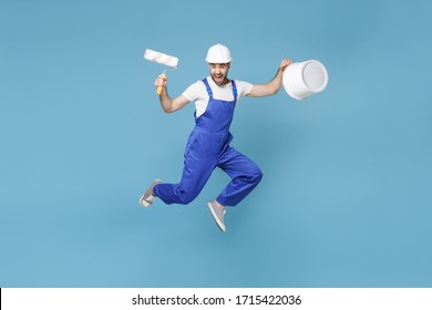Screaming young man in coveralls protective helmet hardhat hold paint roller, bucket isolated on blue wall background. Instruments accessories renovation apartment room. Repair home concept. Jumping