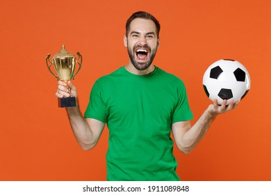 Screaming young man football fan in green t-shirt cheer up support favorite team with soccer ball hold golden cup isolated on orange background studio portrait. People sport leisure lifestyle concept