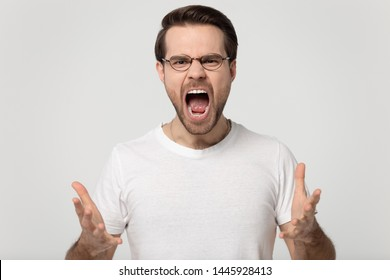 Screaming young man looking at camera open mouth having expressive mad face gesticulates pose isolated on gray studio background, hysterical nervous guy in glasses white t-shirt yelling shouting loud