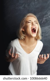 Screaming young woman at darck studio background. Desperate girl yelling, psychological treatment exercise or emotional stress concept
