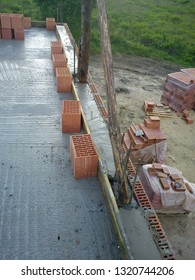 The screed made of concrete, some red bricks on the concrete floor, the first floor of a house under construction, some logs of wood, a construction site