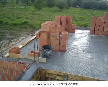 The screed made of concrete, some red bricks, planks of wood and a plastic bucket on the concrete floor, the first floor of a house under construction