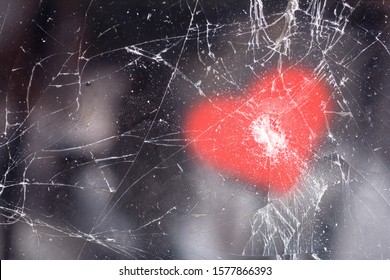 Screen of a broken mobile phone with cracks in the glass and a pattern in the shape of a heart on top