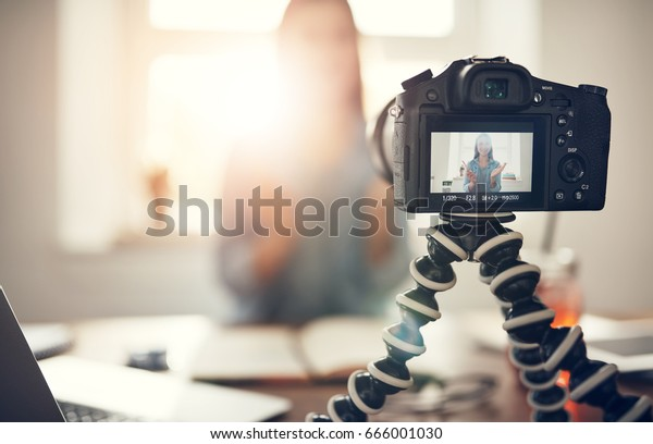 Screen of camera recording a young female blogger gesturing while making a video.