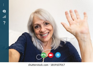 Screen of happy senior woman waving at camera while making video call at home - Focus on face