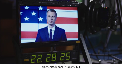 Screen on a monitor in a recoding studio showing a news presenter in front of a National flag with elapsing time below during production and filming.