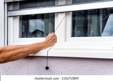 Screen on window. hand holds anti-insect mosquito net on pvc window