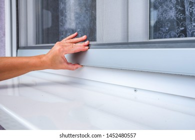 Screen on window. Woman hand holds anti-insect mosquito net on pvc window