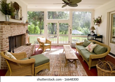 screen porch with fireplace and wicker furniture