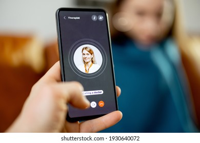 A screen of Smartphone with calling a doctor while woman covered with a plaid on background. Focus on display. Close up