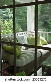 Screened in furnished porch viewed through door leading into house
