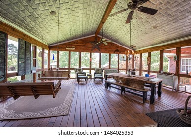 Screened porch with furniture and wood floor