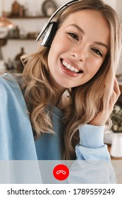 Screenshot of happy blonde woman smiling and using headphones while making video call