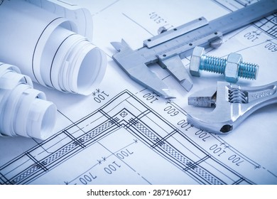 Screw bolt with nut adjustable spanner slide caliper rolls of construction plans on blueprint architecture and building concept.