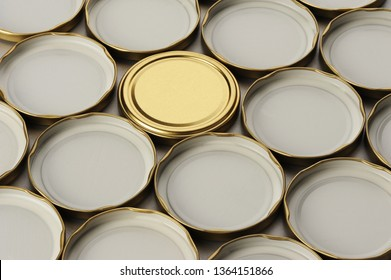 Screw cap for glass jars. For canning, canned food. One golden cap on gray background and flip covers