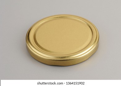 Screw cap for glass jars. For canning, canned food. Golden cap on gray background