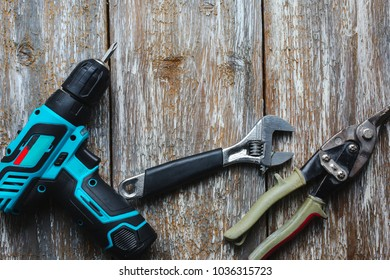 Screw gun, wrench, snips are lying on the old wooden background. Working instruments on the texture for maintenance repairing works.